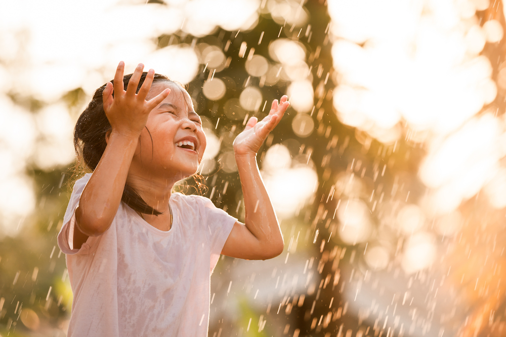 A little girl playing outside in the water, smiling