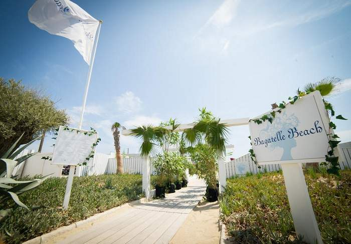 Bagatelle Beach in St Tropez_Entrance of the beach club_White flat floating in the wind, palm trees and greenery_Sunshine_Bagatelle Beach sign